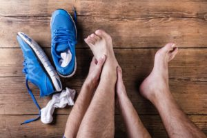injured-runner-holding-his-ankle-and-the-top-of-his-foot